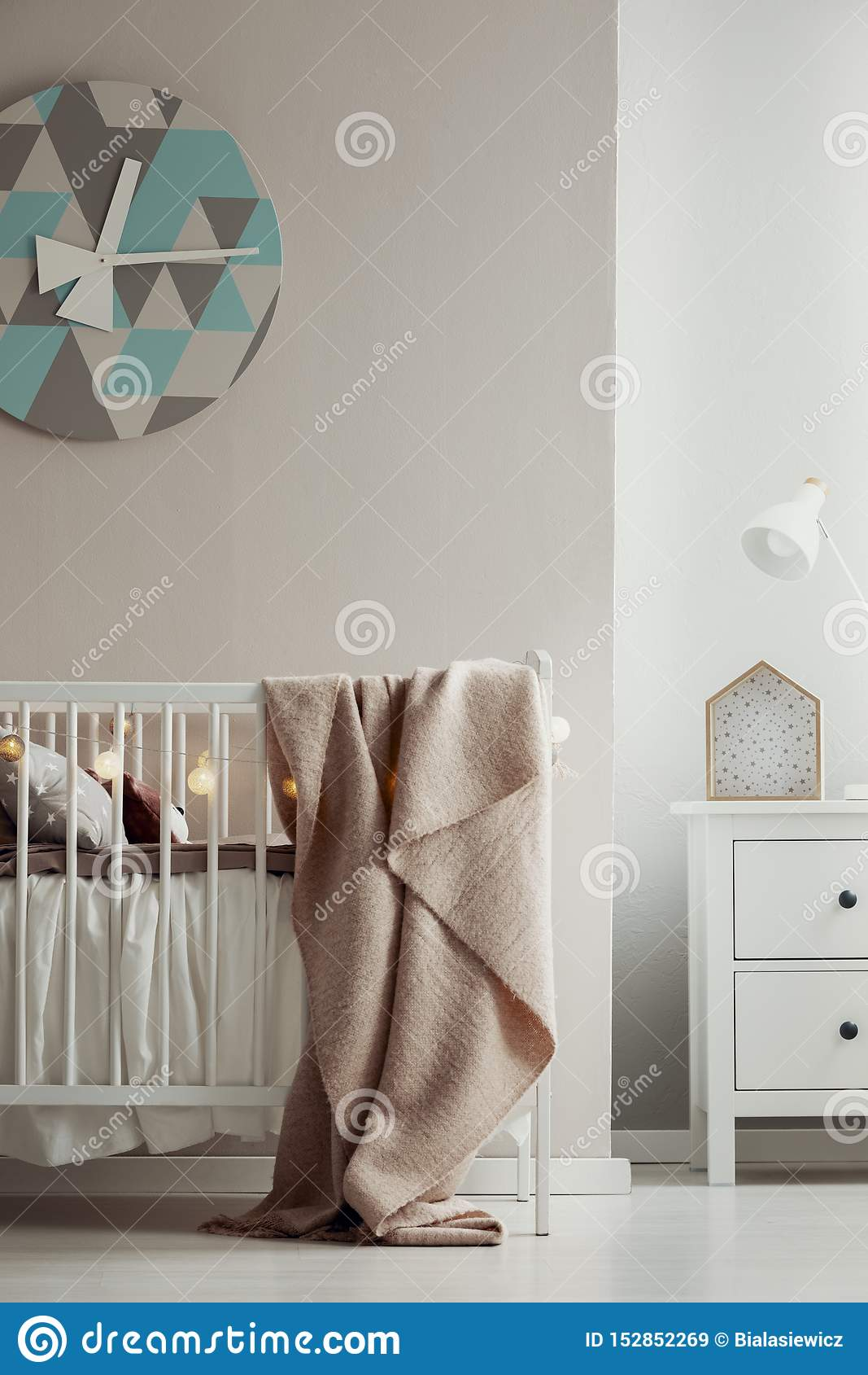 Fancy clack on the wall of elegant baby bedroom interior with white wooden crib with pastel pink blanket and cotton ball lights