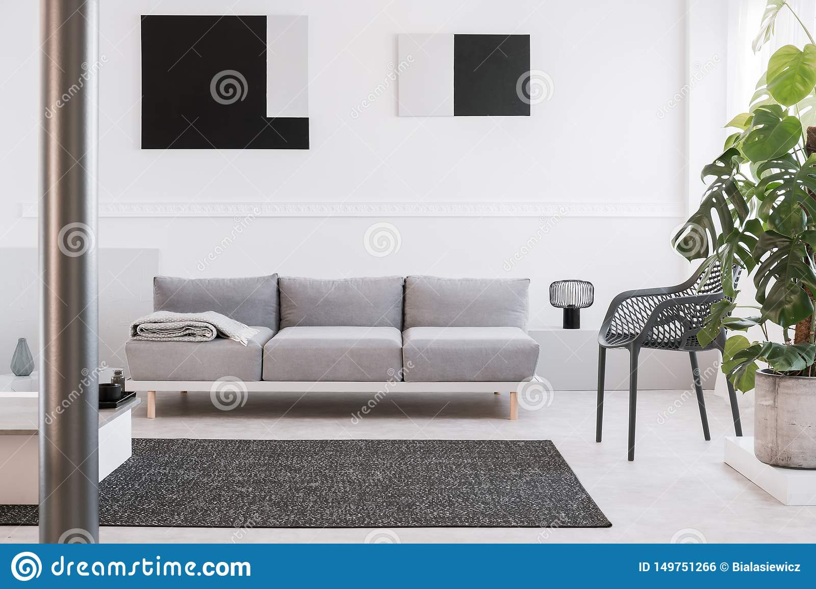 fancy grey metal chair next to comfortable couch in bright