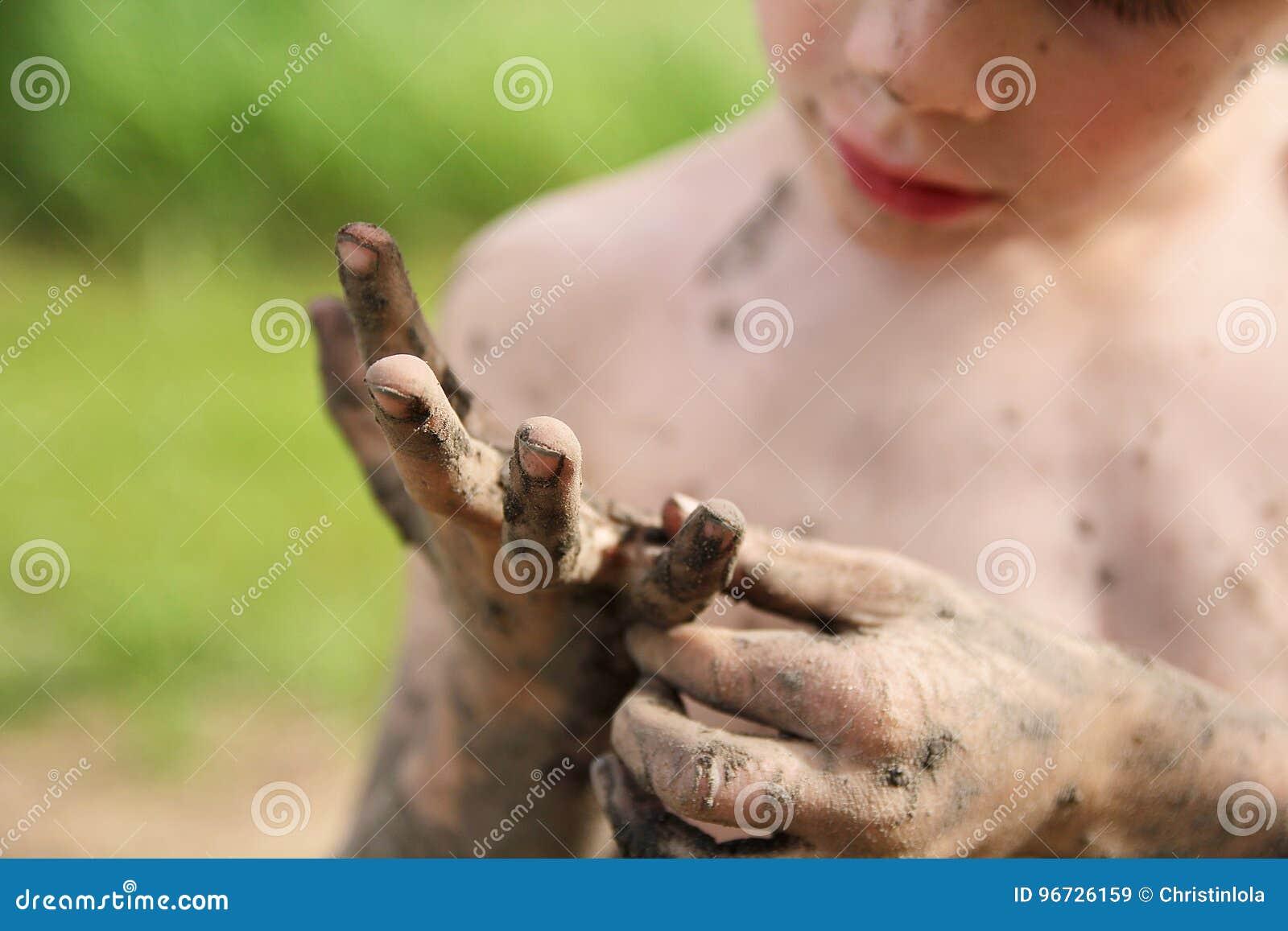 Fango di raccolto di Little Boy fuori dalle sue mani sporche