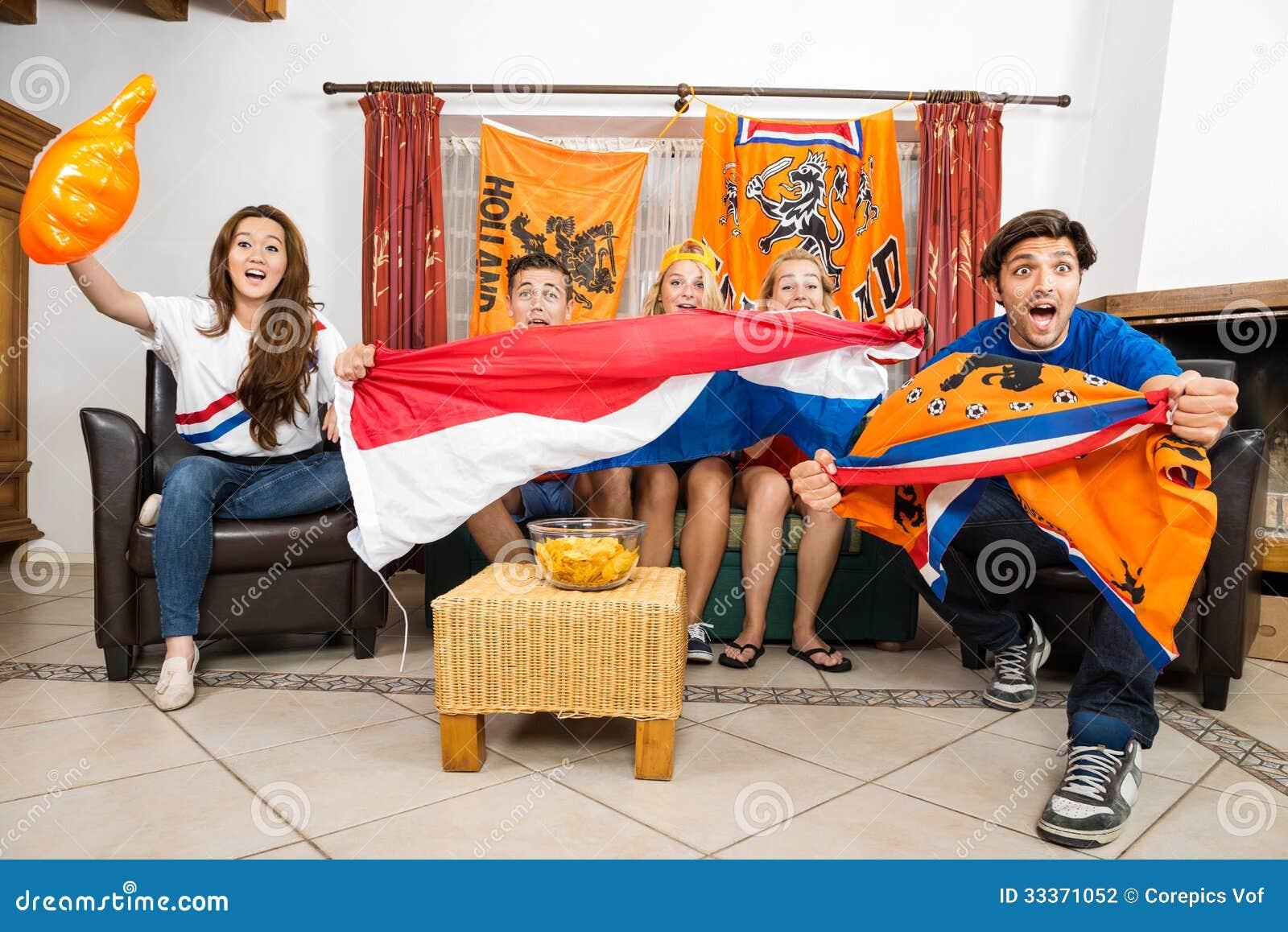Fans de foot encourageant tout en regardant la rencontre à la maison