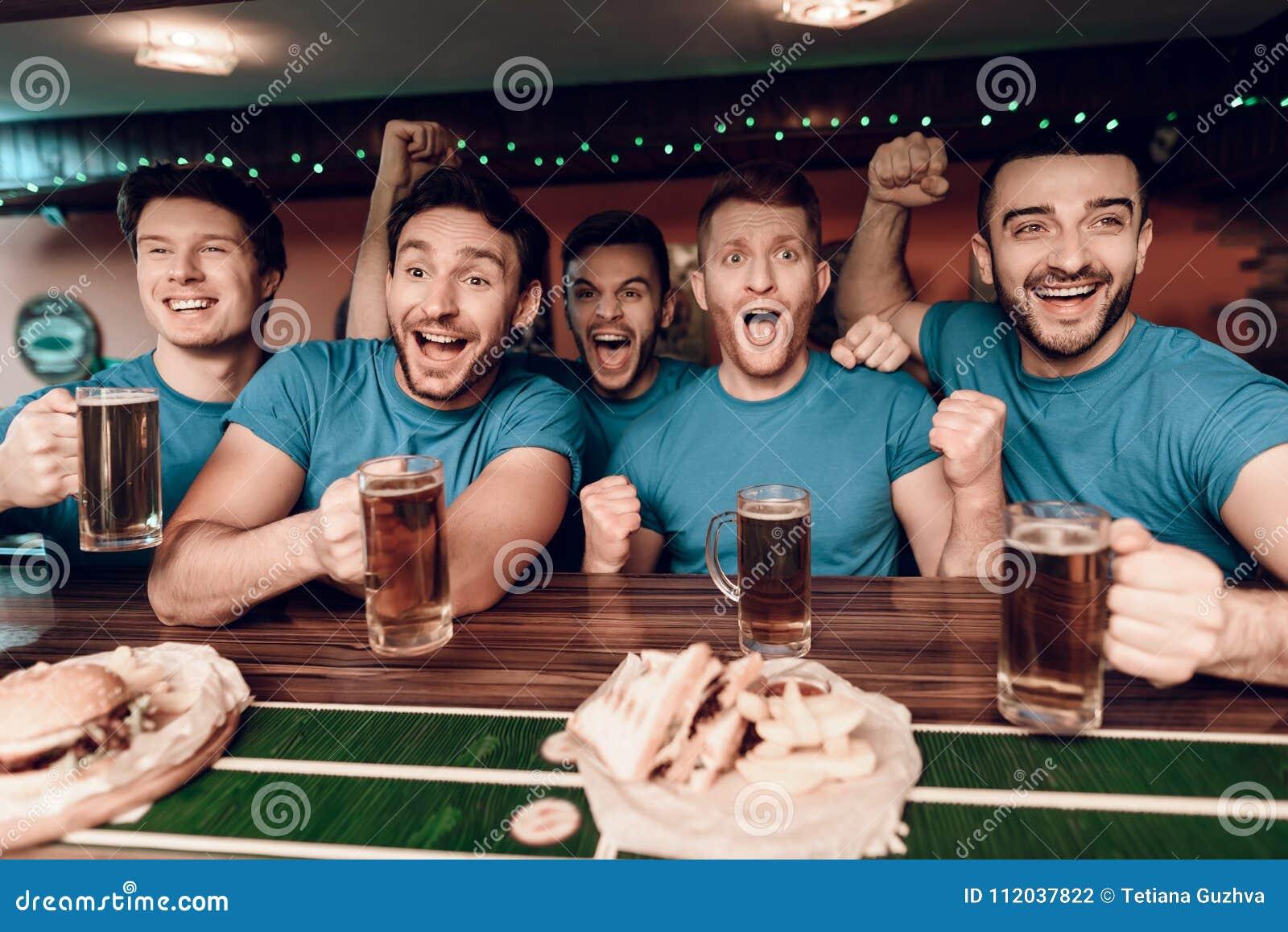 Fans de foot observant la bière potable de jeu et mangeant à la barre de sports