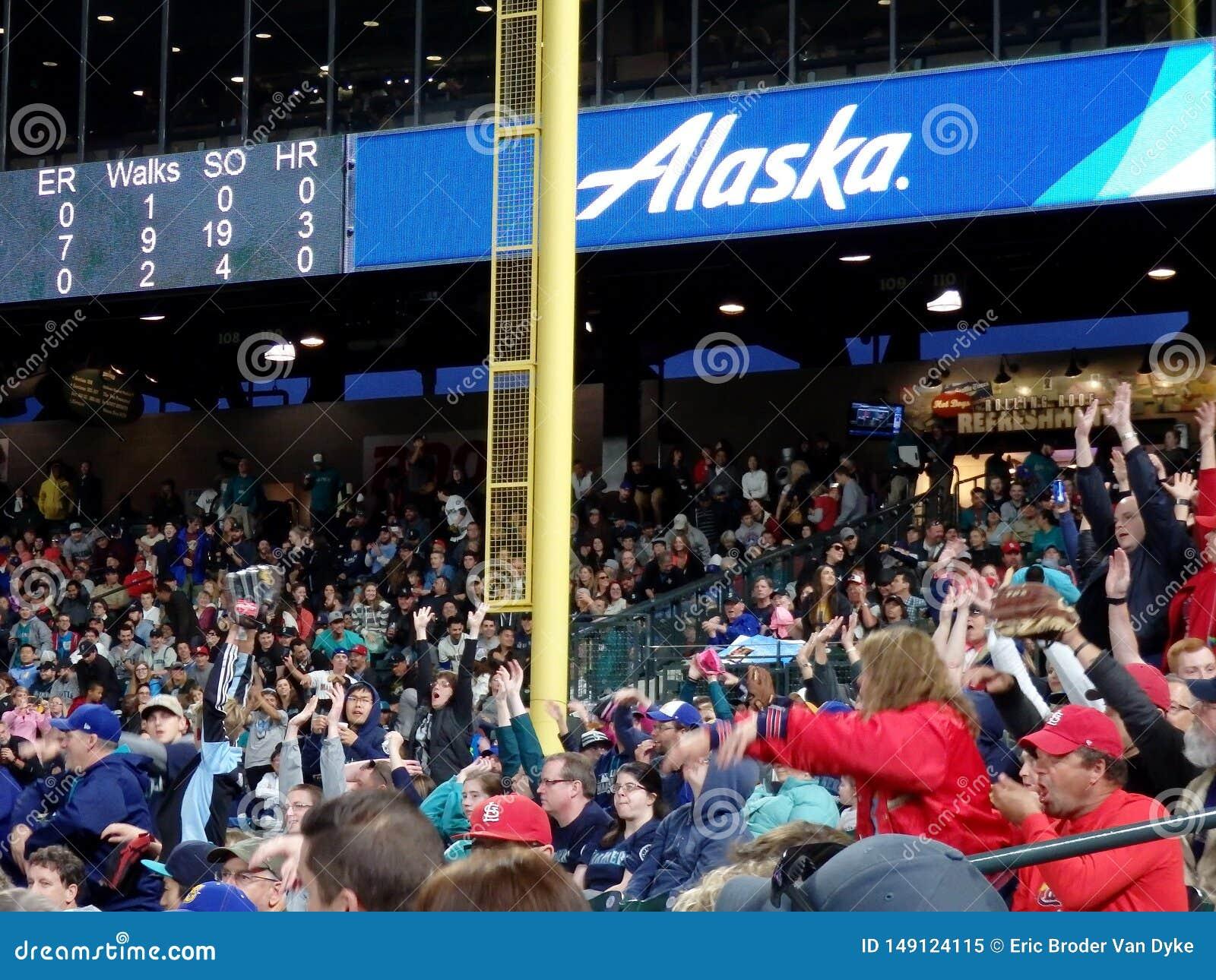 Fans in den Zuschauertribünen tun die Welle mit Anzeigetafel über der Aufmachung von Alaska Airlines-Anzeige