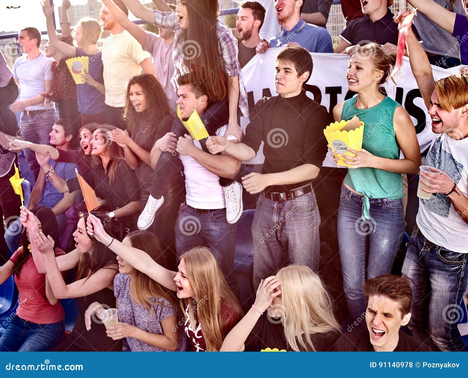 Fans encourageant dans le stade et mangeant du maïs éclaté