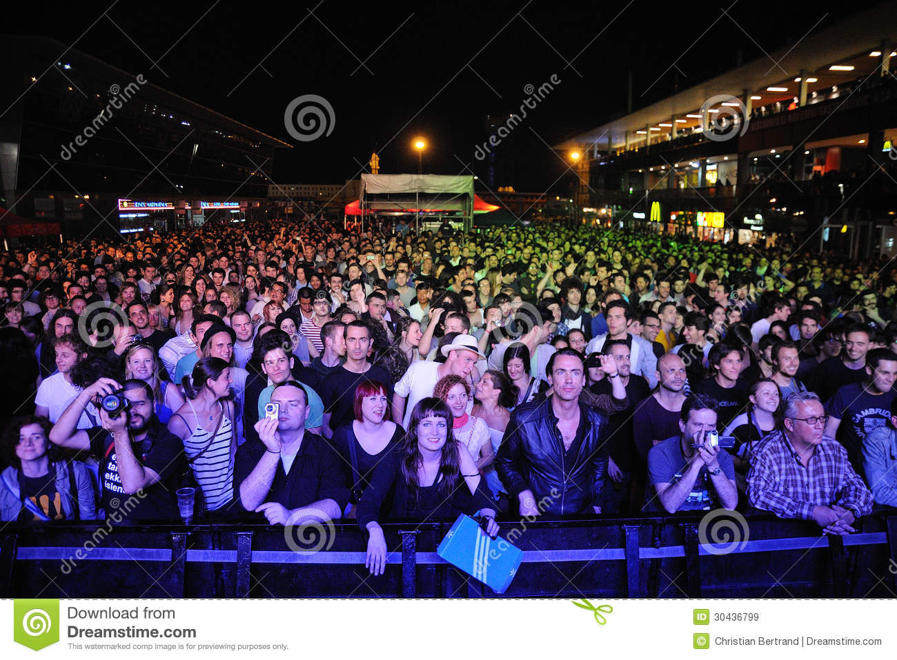 Fans taking pictures with cell phone behind barrier stock photo - Fans At Maremagnum Waiting For A Concert Royalty Free Stock Images