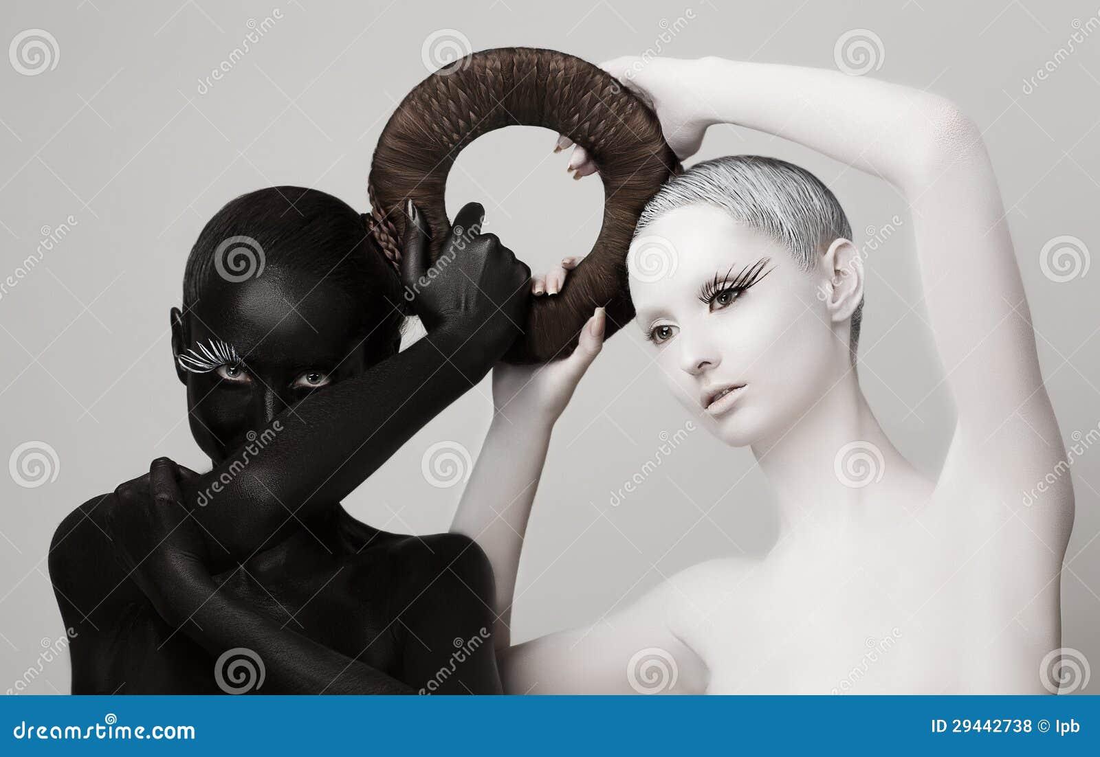 Fantasía. Símbolo esotérico de Yin y de Yang. Siluetas de las mujeres negras y blancas