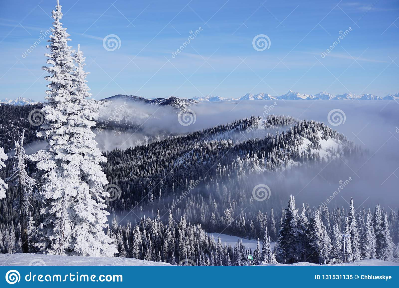 Fantasma da neve que negligenciam o vale nuvem-coberto e picos que espreitam acima dele no recurso do peixe branco