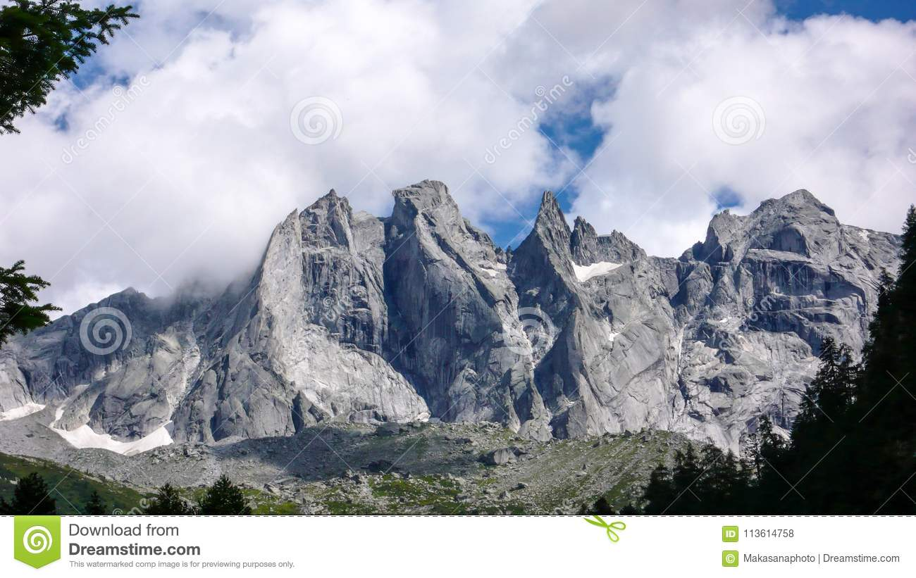 Fantastic mountain landscape in the Swiss Alps with jagged sharp granite peaks under a cloudy sky