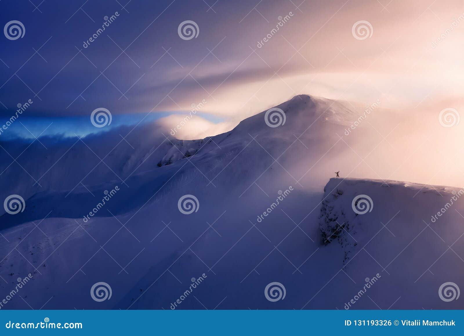 Fantastisch landschap met een vrije ruiter en een bergbeklimmer, hooggebergte in sneeuw en de mist met interessante kleur