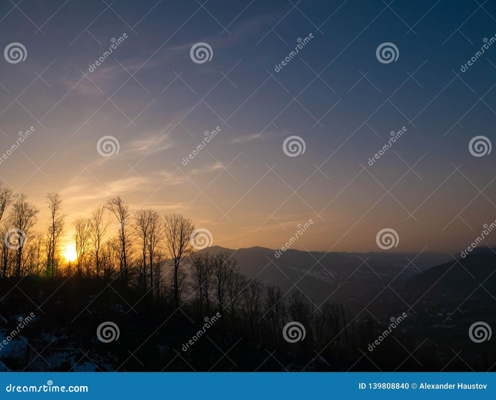 Fantastisk och härlig sikt av bergen i strålarna av inställningssolen