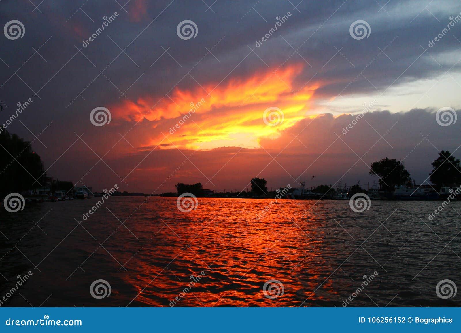 Fantastisk orange solnedgång mellan moln över vatten