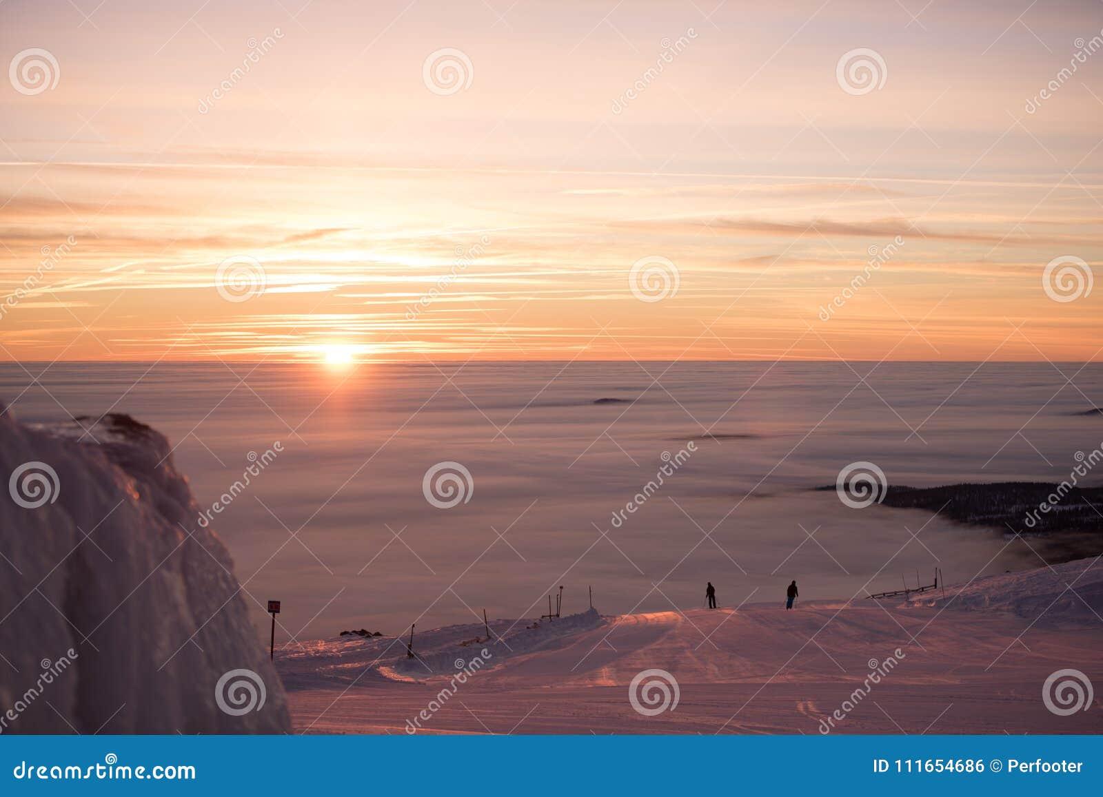 Fantastisk rosa himmel och berg lite varstans Vänner som har gyckel överst av berget, medan skida/snowboarding Hisnande solnedgån