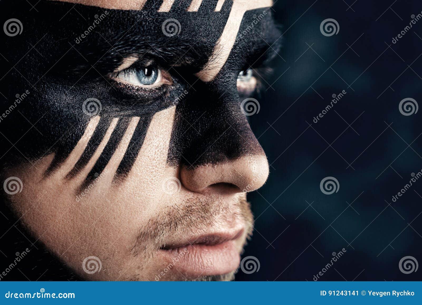 Fantasy art makeup. man with black painted mask on face. Close up Portrait. Professional Fashion Makeup.
