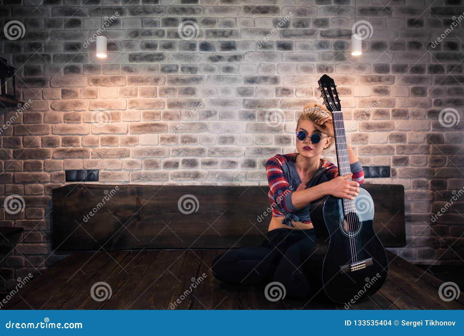Fantazyjności dziewczyna siedzi na łóżku z gitarą
