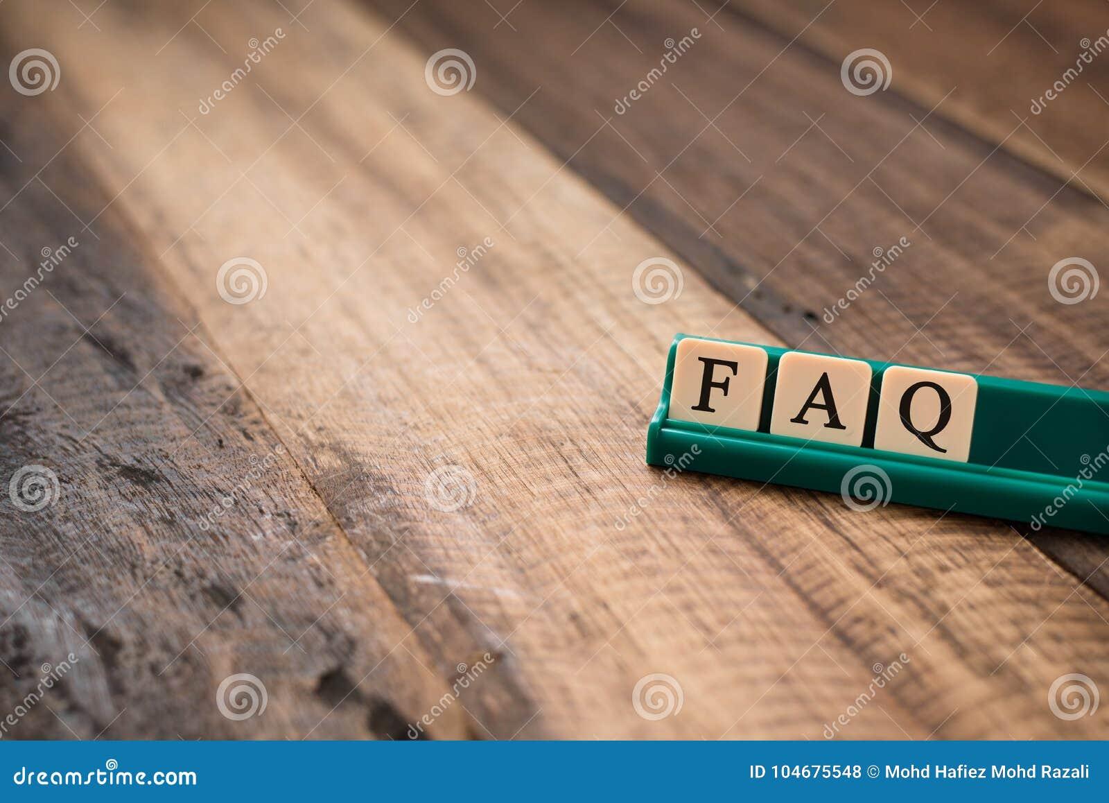 FAQ-Wort auf Alphabetfliesen auf Holztisch bitten Sie häufig um Fragenkonzept