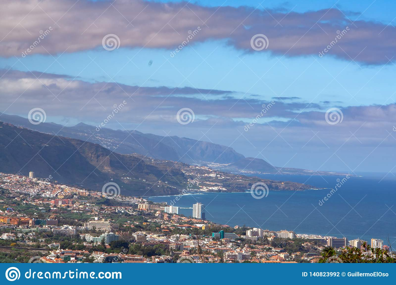 Far view from a mountain on wild coast with City