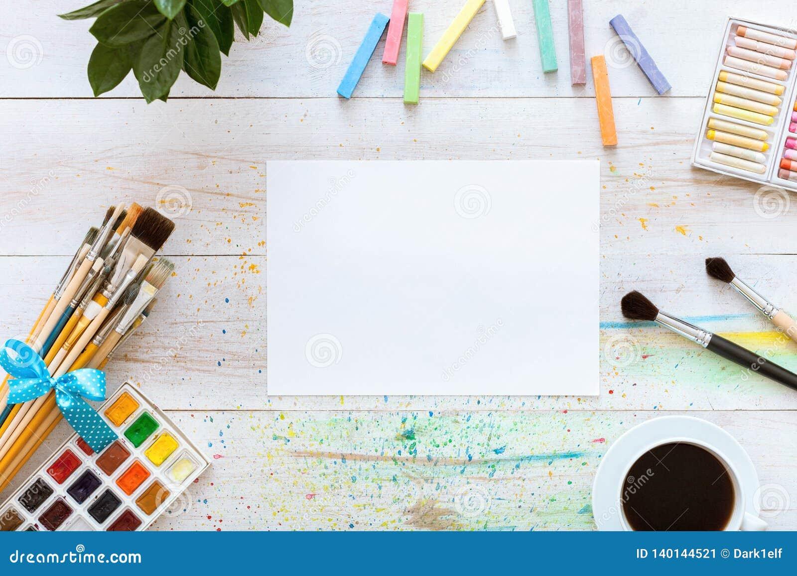 Farb muśnięcia, paintbox z akwarelami, kredki, kawa i puste miejsce, wyśmiewają w górę papieru na białym drewnianym tle, artystyc