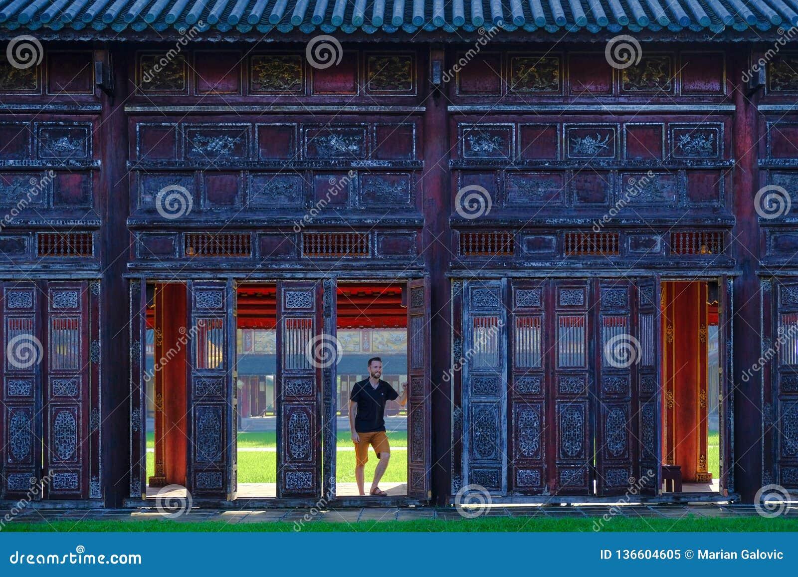 Farbe/Vietnam, 17/11/2017: Mannstellung nahe bei dekorativen Türen in einem traditionellen pavillion im Zitadellenkomplex in der