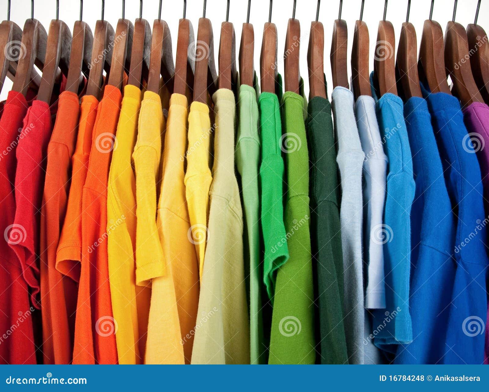 Farben des regenbogens kleidung auf hölzernen aufhängungen