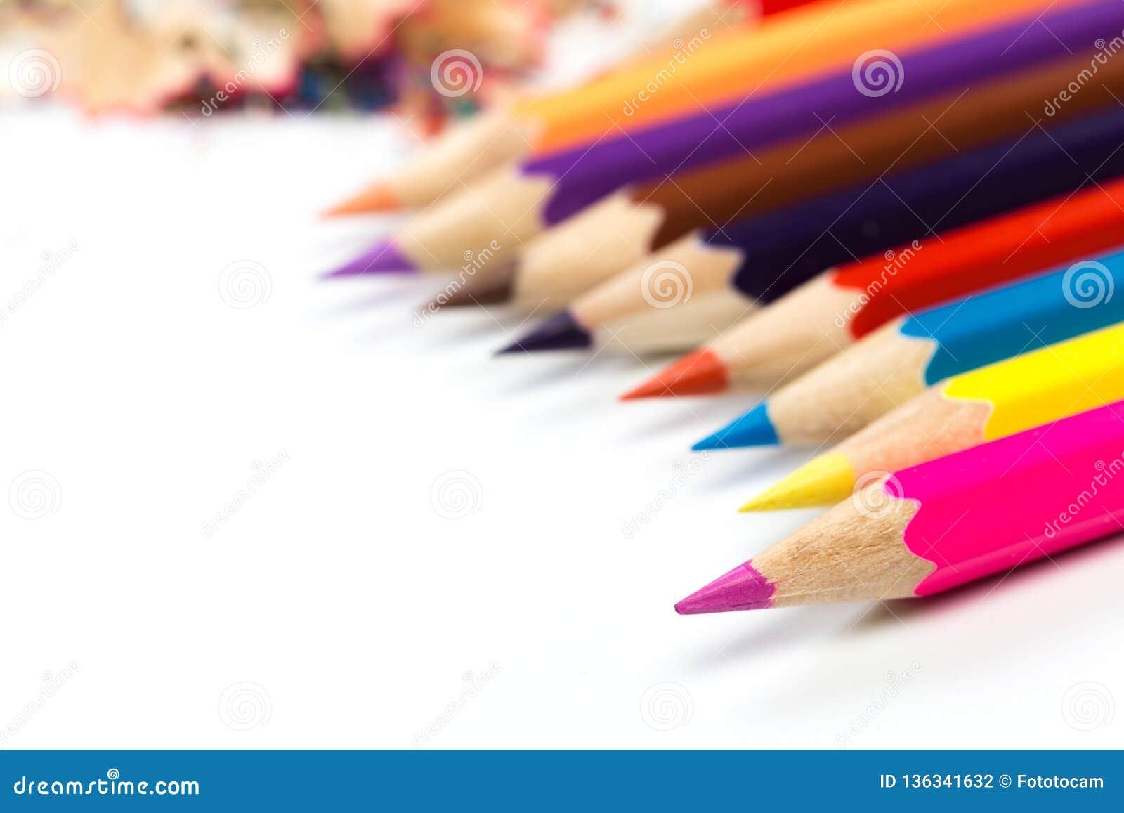 Farbige Bleistifte und Schnitzel mit Bleistiften Bleistiftspitzer von Bleistiften auf einem weißen Hintergrund