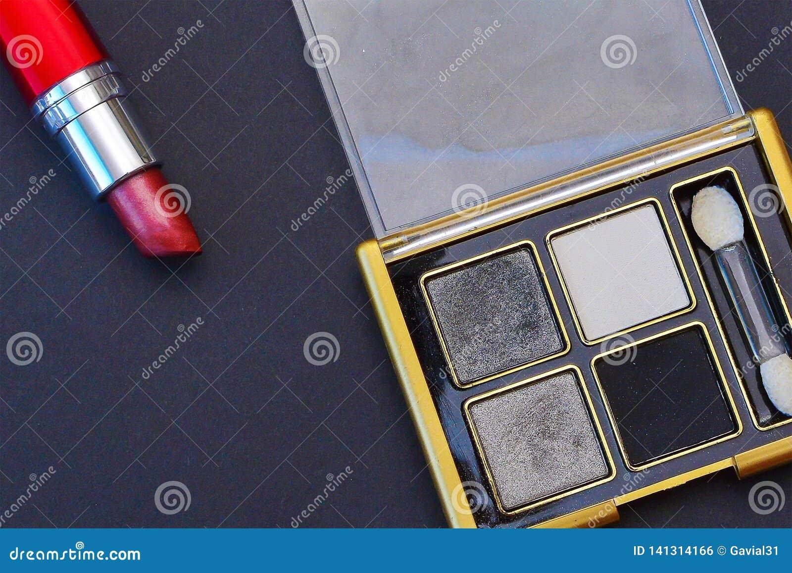 Fard à paupières et rouge à lèvres cosmétiques sur un fond noir