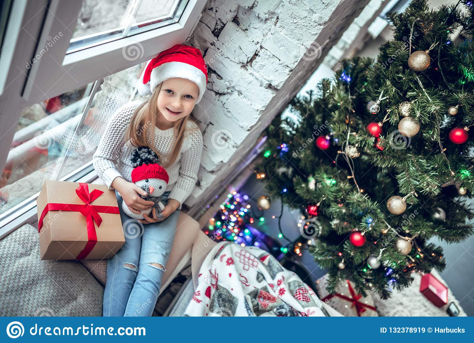 Fare da baby-sitter felice sulla finestra con regalo di Natale