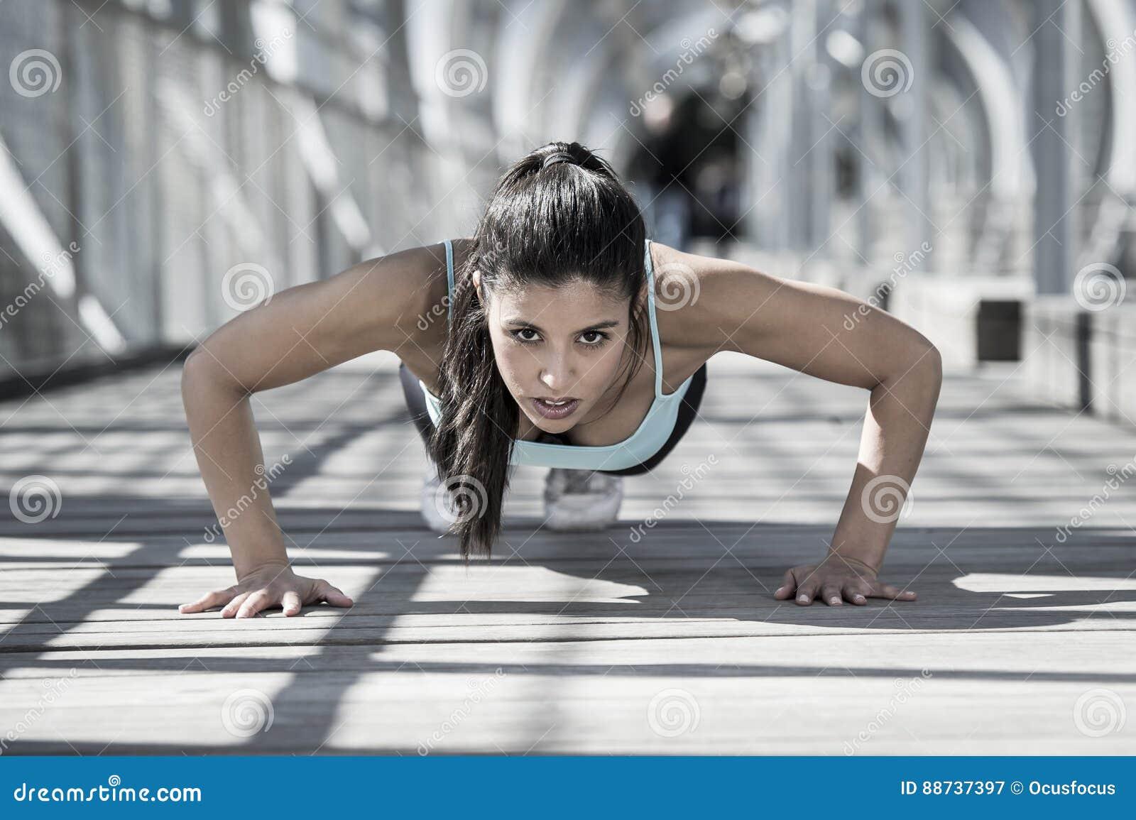 Fare della donna di sport atletico spinge verso l alto prima di correre nell allenamento urbano di addestramento
