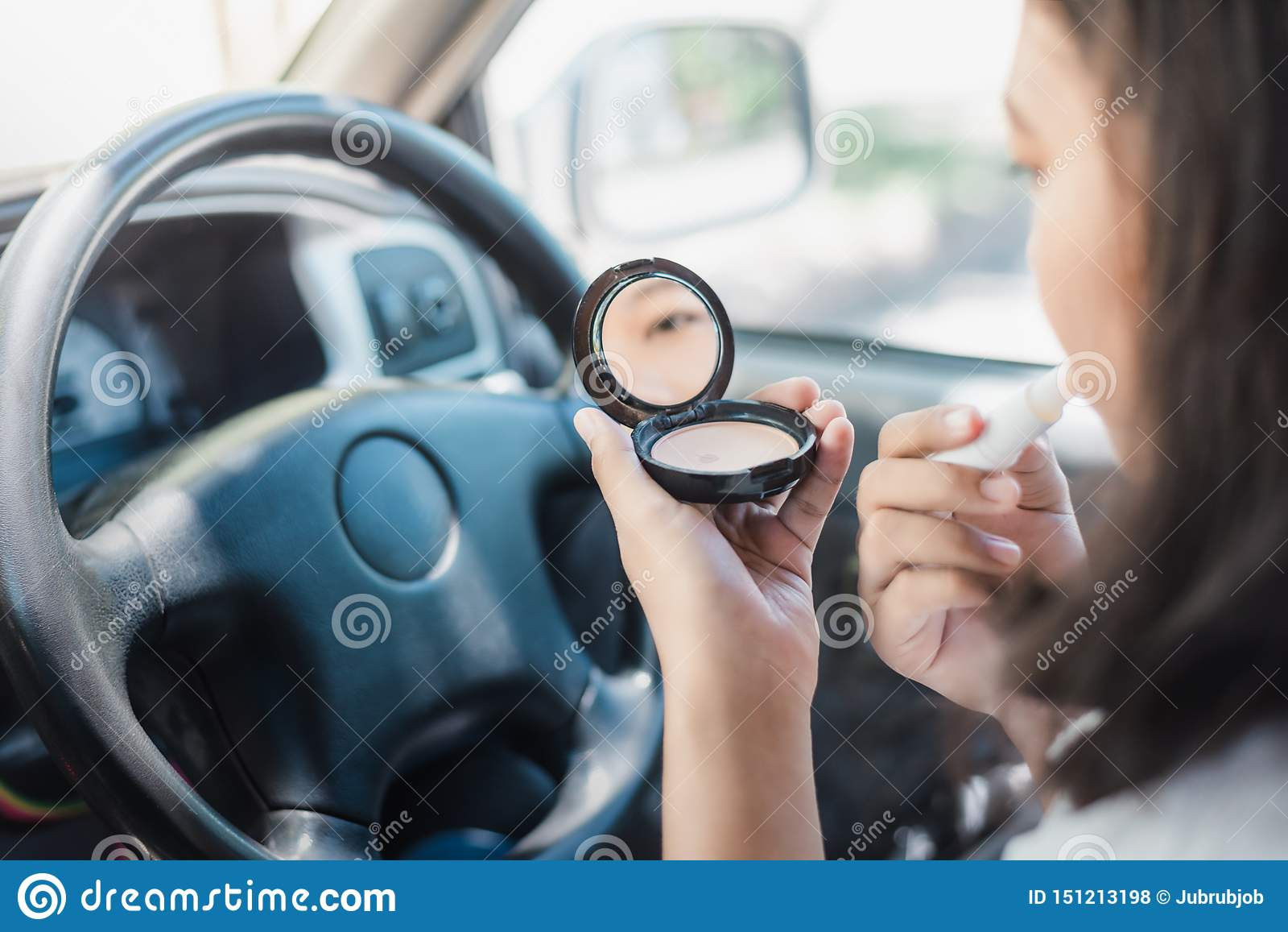 Fare della giovane donna compone in automobile, rossetto della pittura