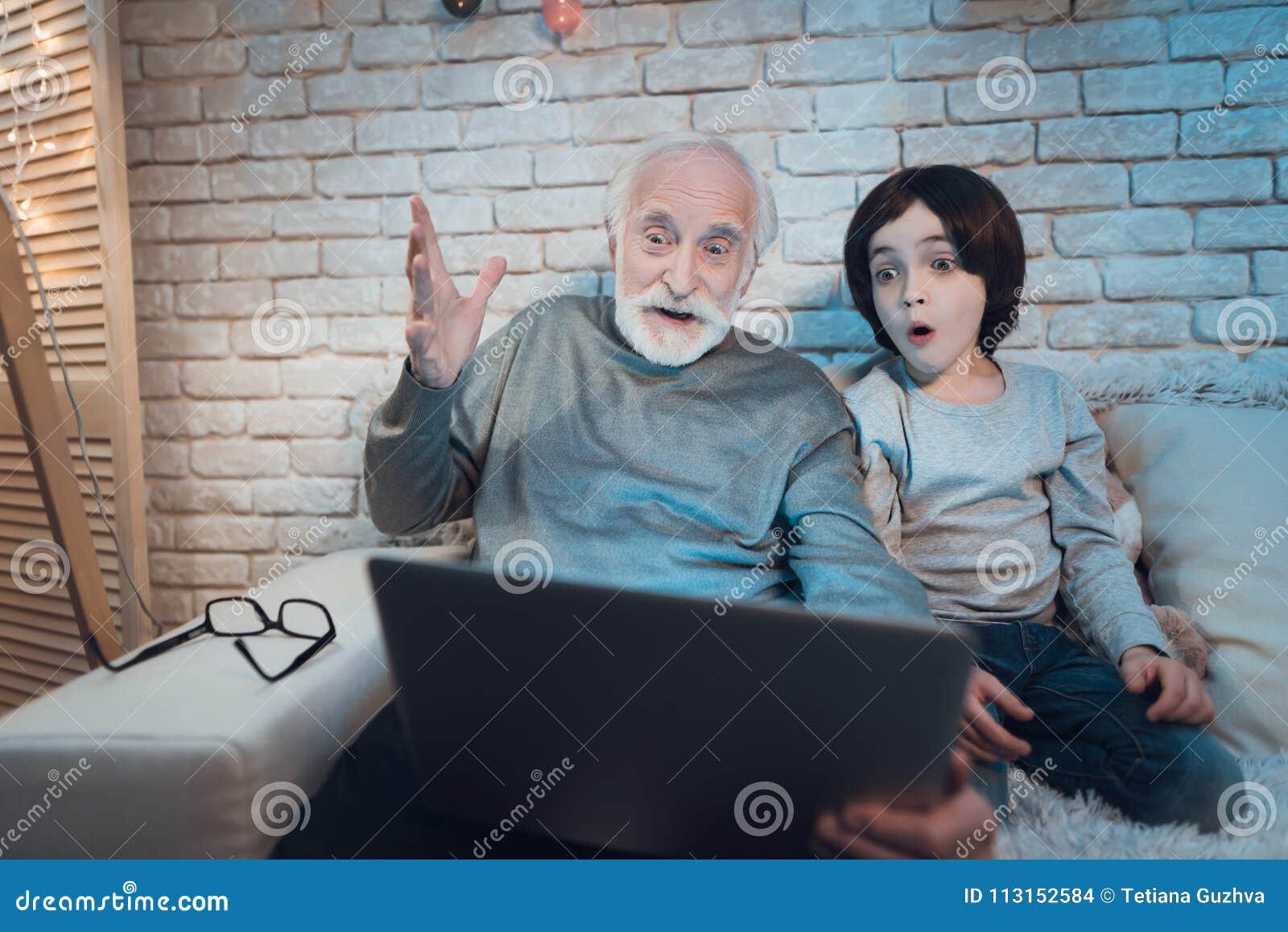 Farfadern och sonsonen sitter hållande ögonen på intressant film på natten hemma
