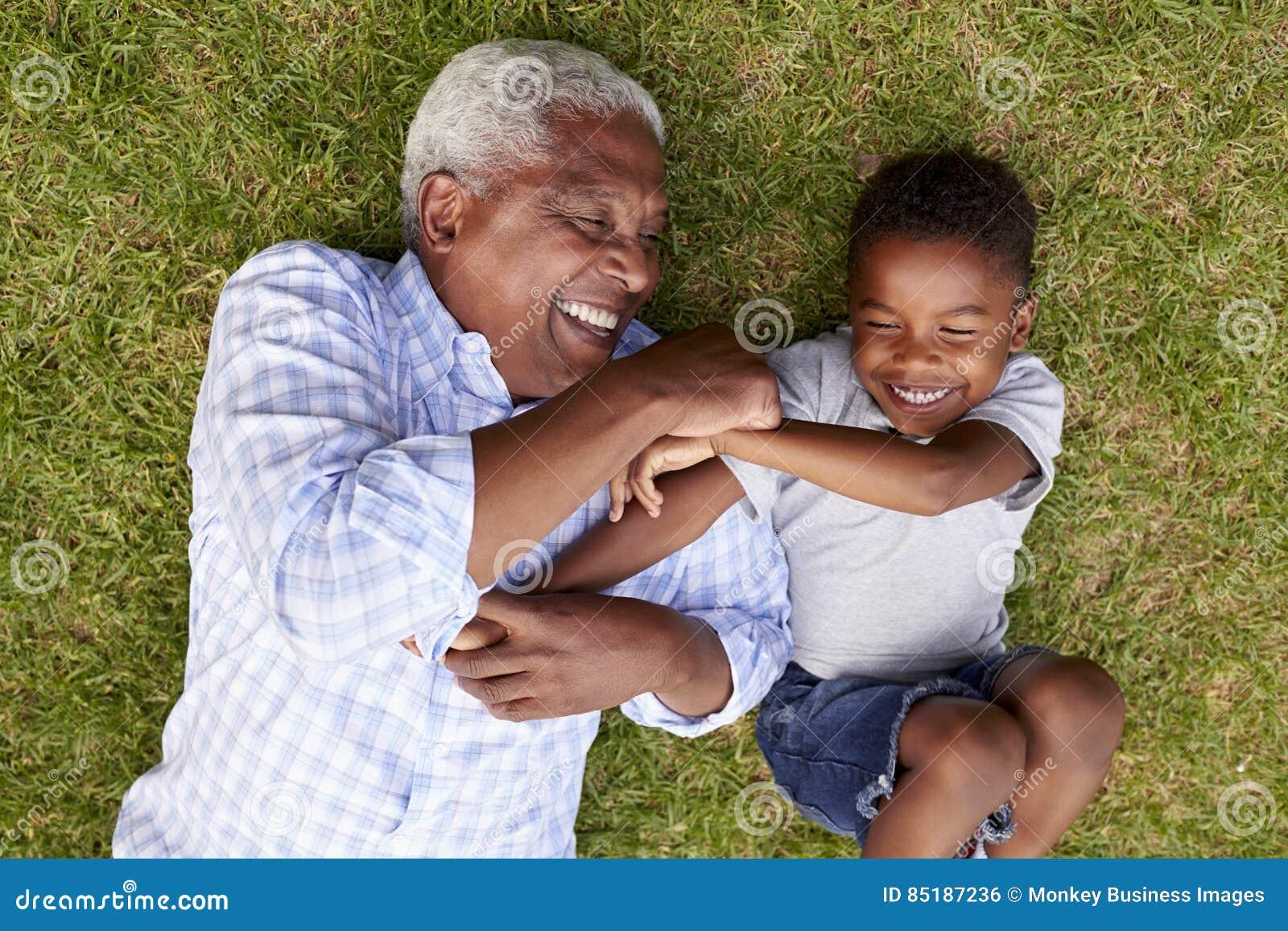 Farfadern och sonsonen spelar att ligga på gräs, flyg- sikt