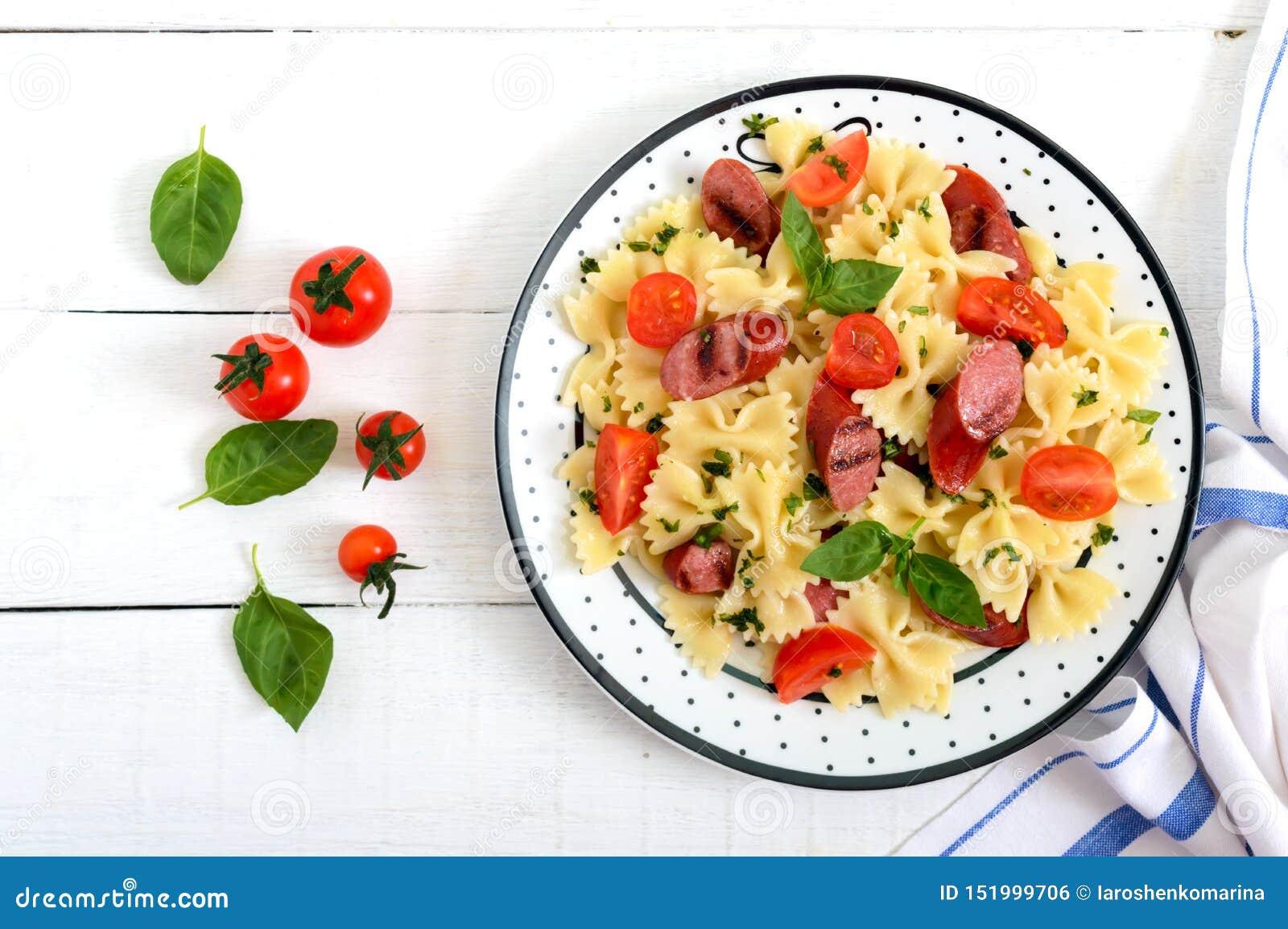 Farfalle saporito della pasta con le salsiccie arrostite, i pomodori ciliegia freschi ed il basilico su un piatto su un fondo di