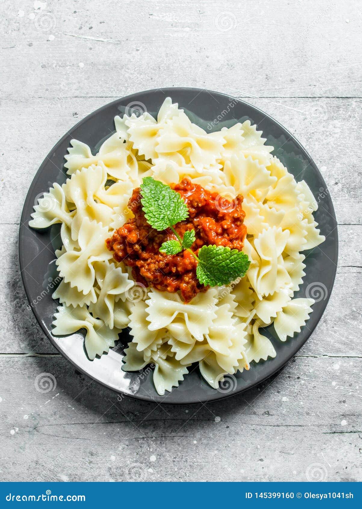 Farfalledeegwaren met Bolognese saus en muntbladeren