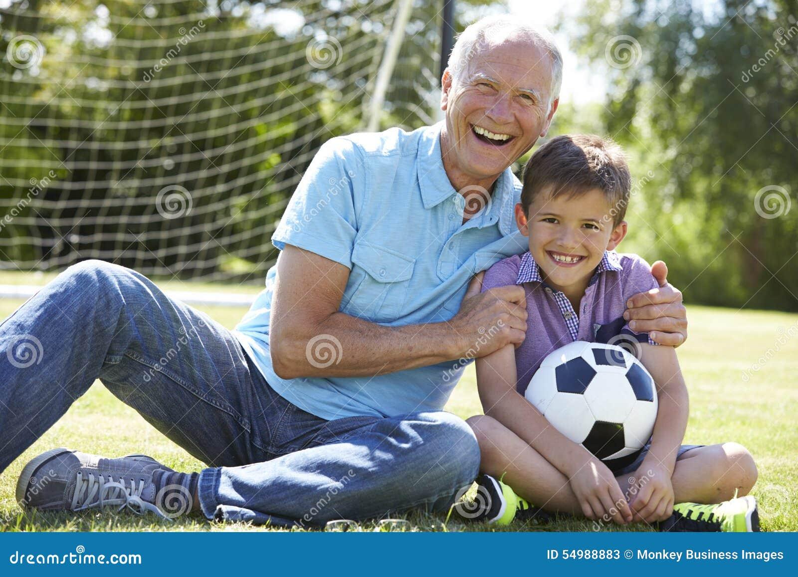 Farfar och sonson som spelar fotboll i trädgård