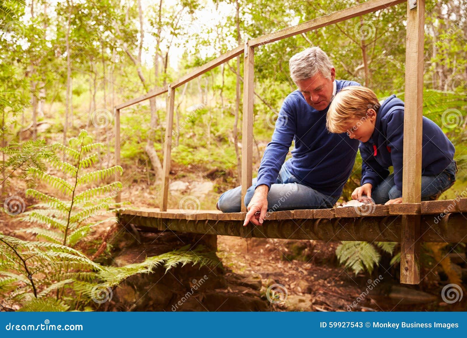 Farfar som spelar med sonsonen på en bro i en skog