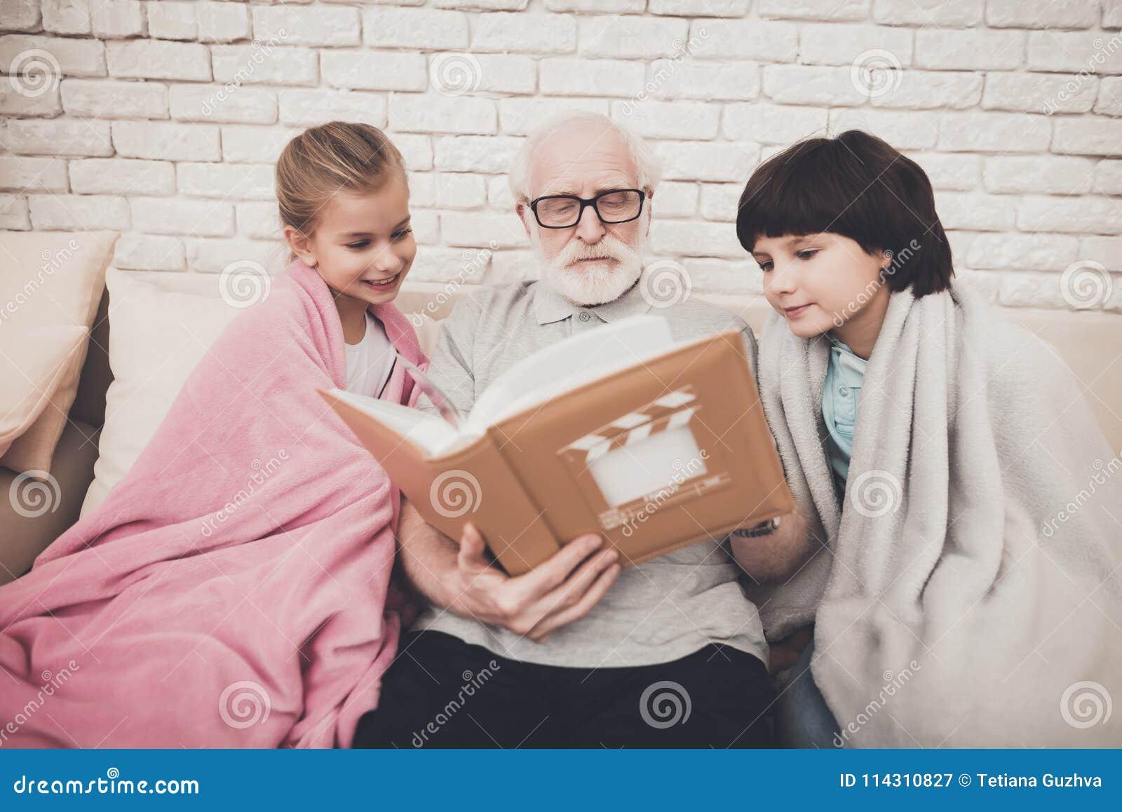 Farfar, sonson och sondotter hemma Morfadern och barn håller ögonen på foto i album