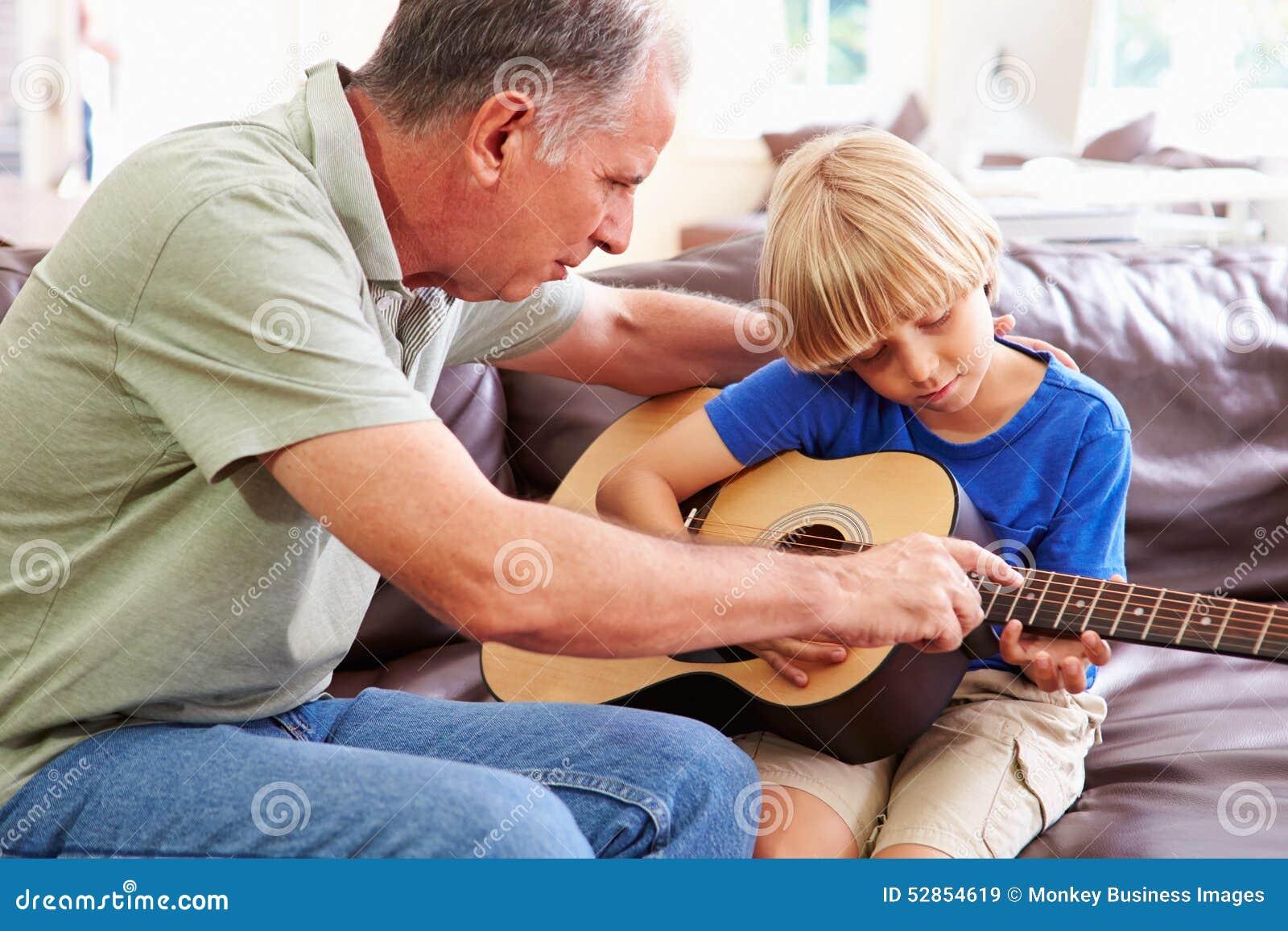 Farfarundervisningsonson som spelar gitarren