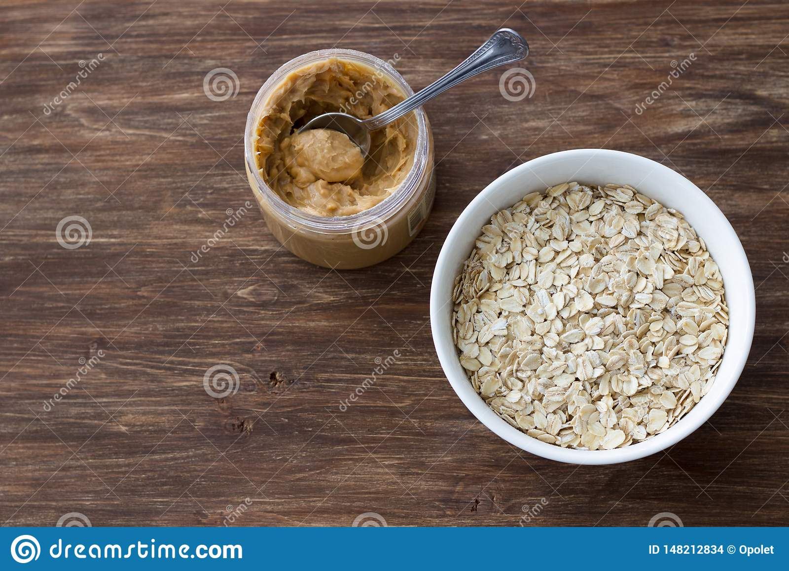 Farine d avoine crue dans une cuvette blanche avec le beurre d arachide, ingr?dients pour un petit d?jeuner sain d?licieux sur un