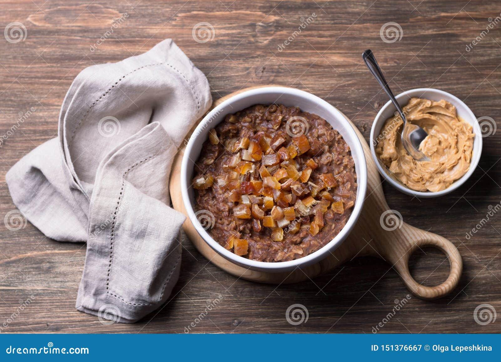 Farine d avoine d?licieuse en cuvette blanche, fruits de dates et cacao Petit d?jeuner sain sur un fond en bois