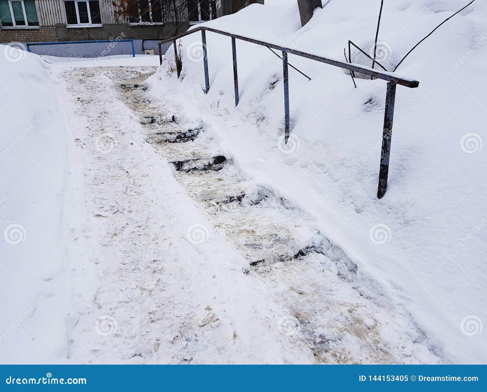 Farlig hal trappa och gammal ledstång i vinter