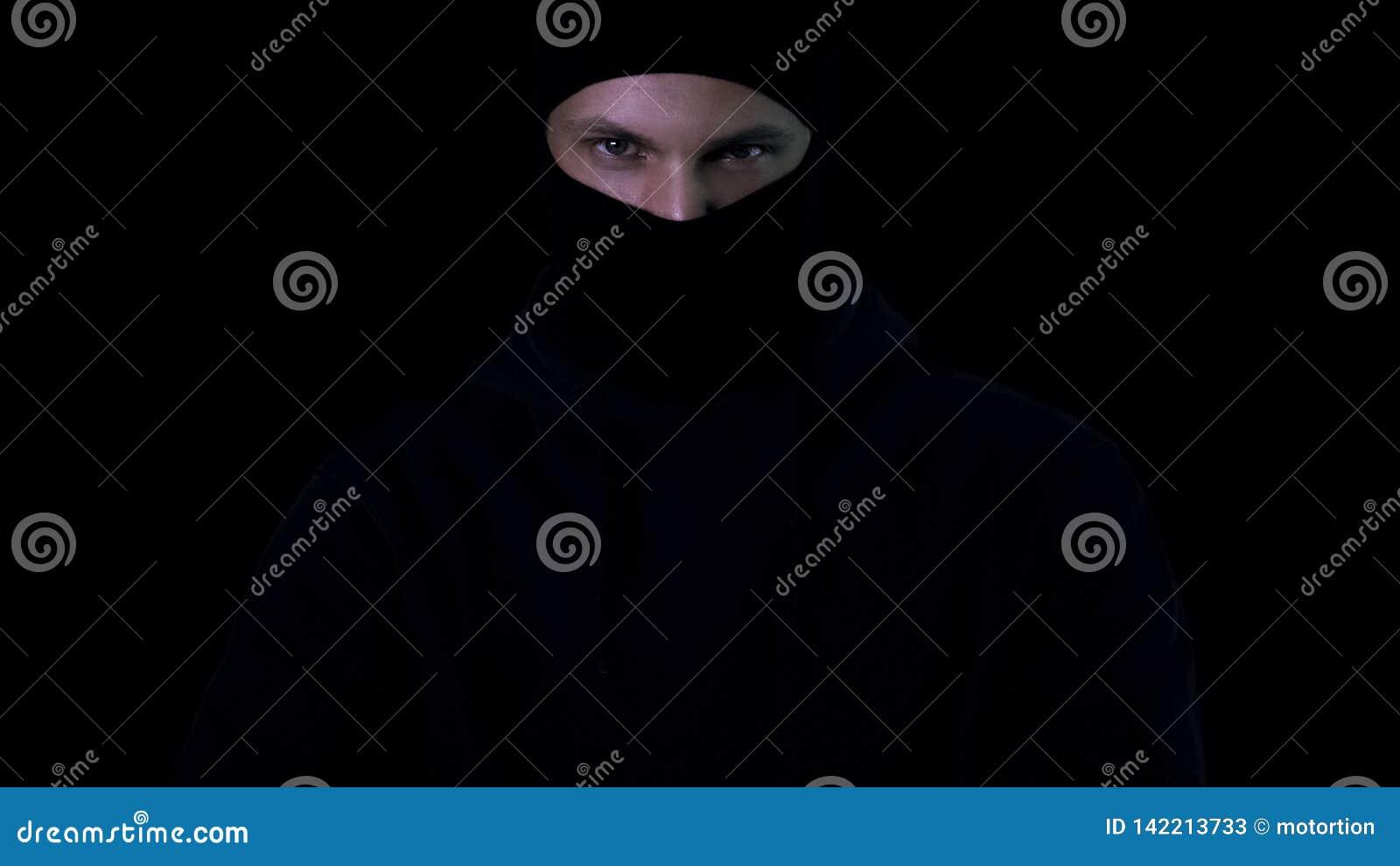 Farlig man i balaclavaen som in camera ser på svart bakgrund, terrorism