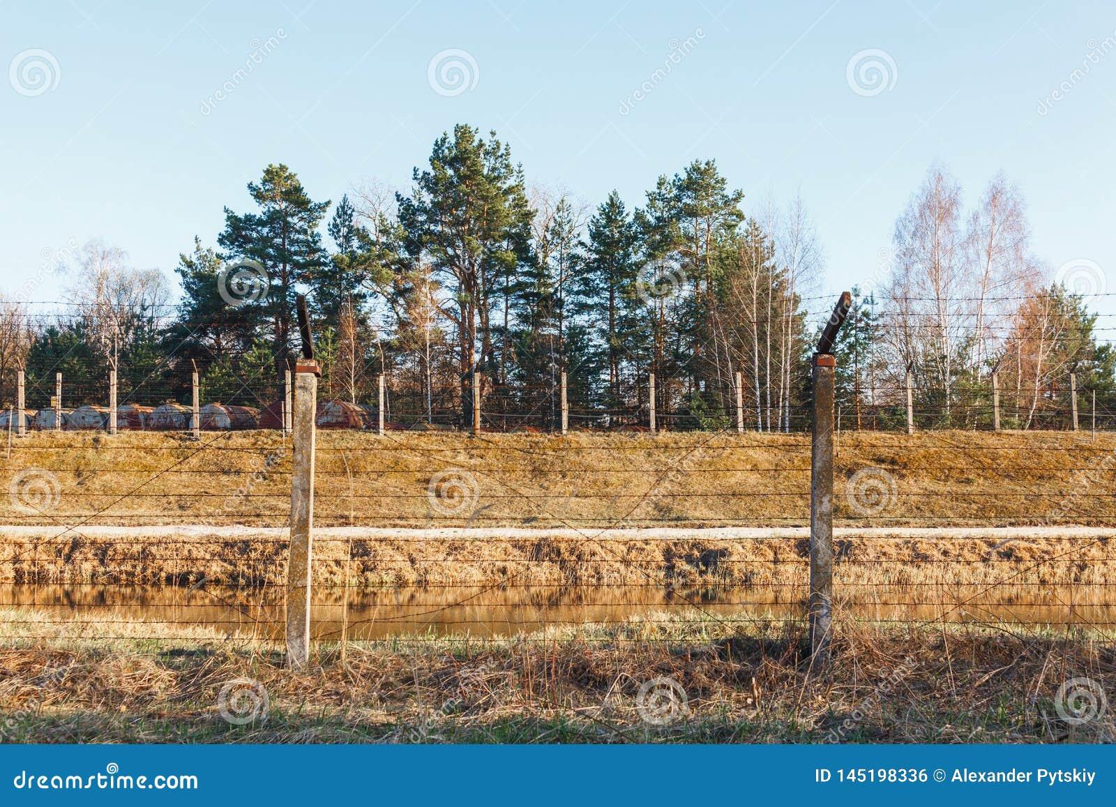 Farligt område som fäktas med taggtrådstaketet