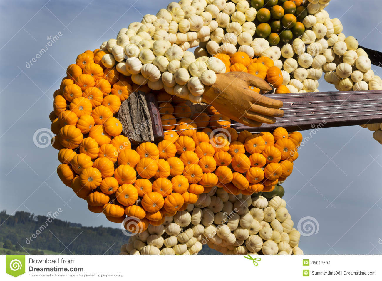 Farm art guitar and guitarist made of small orange, green and white pumpkins close-up