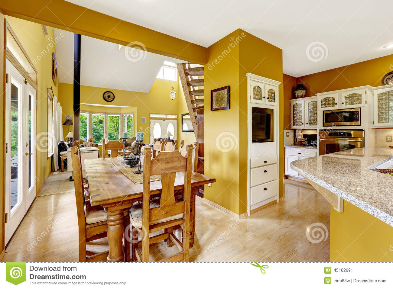 Beautiful farm house interior in bright yellow color wooden dining