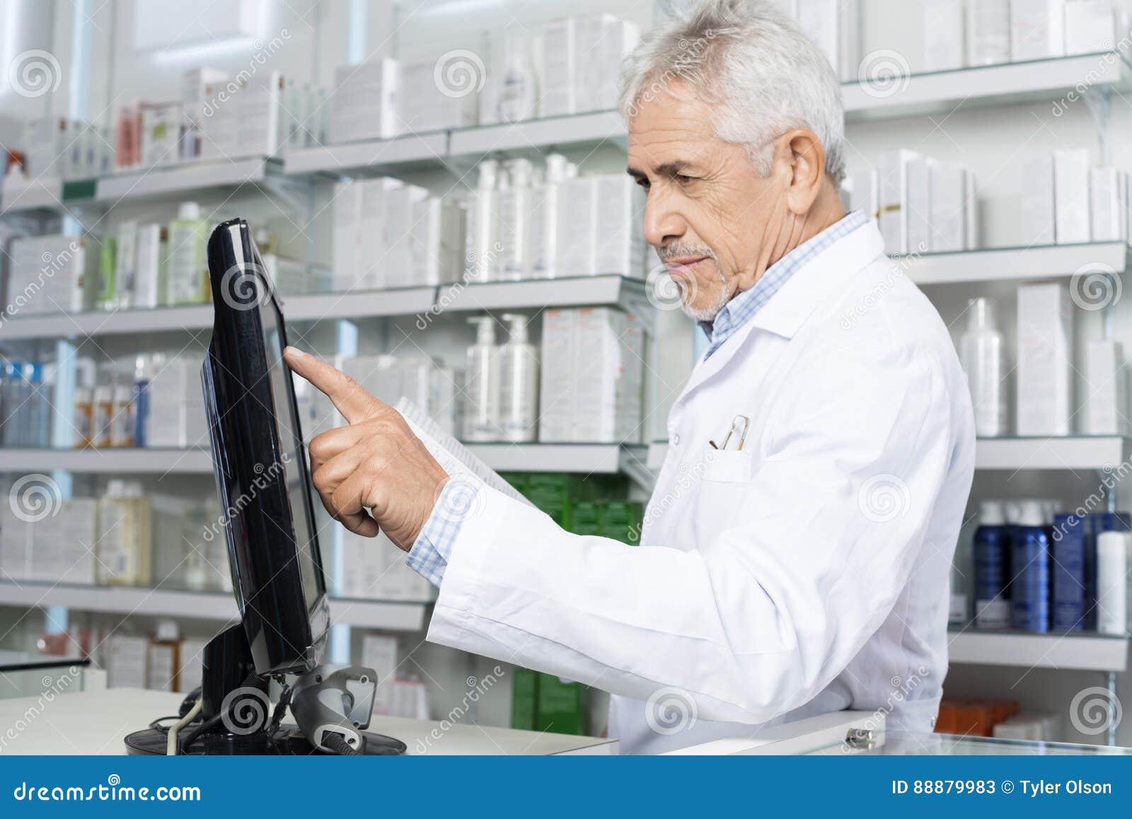 Farmacéutico de sexo masculino Touching Monitor Screen en farmacia