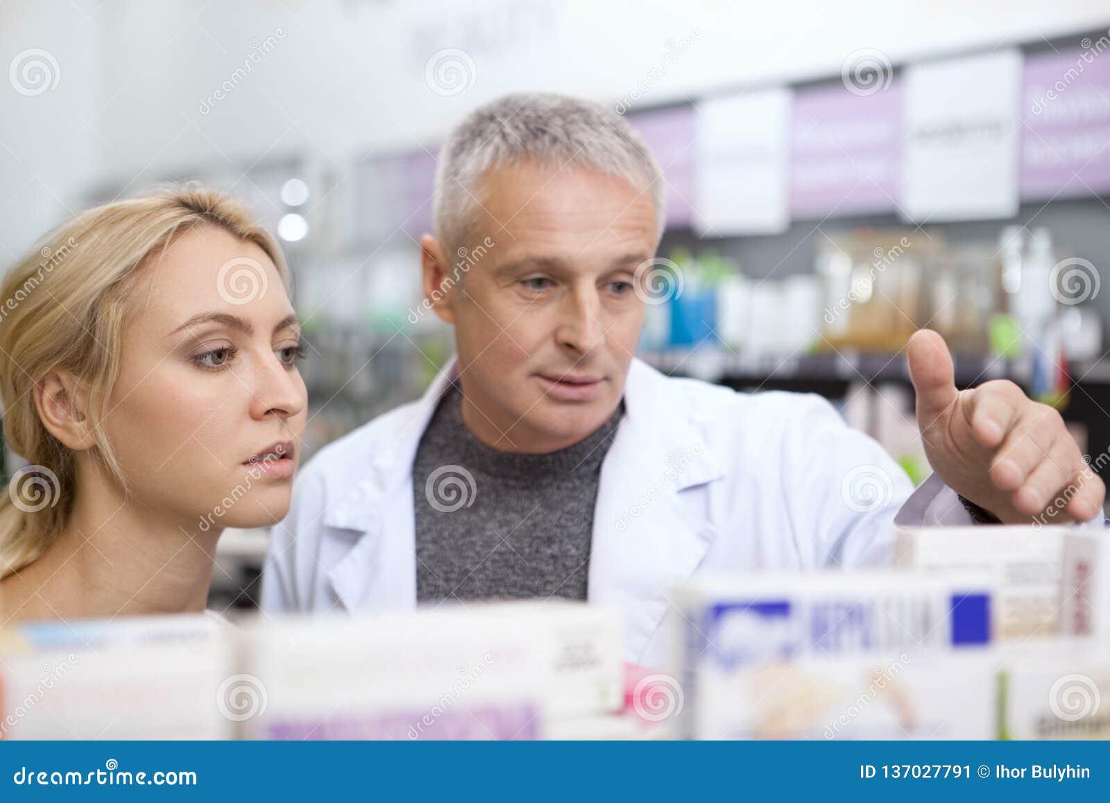 Farmacêutico maduro que ajuda seu cliente fêmea