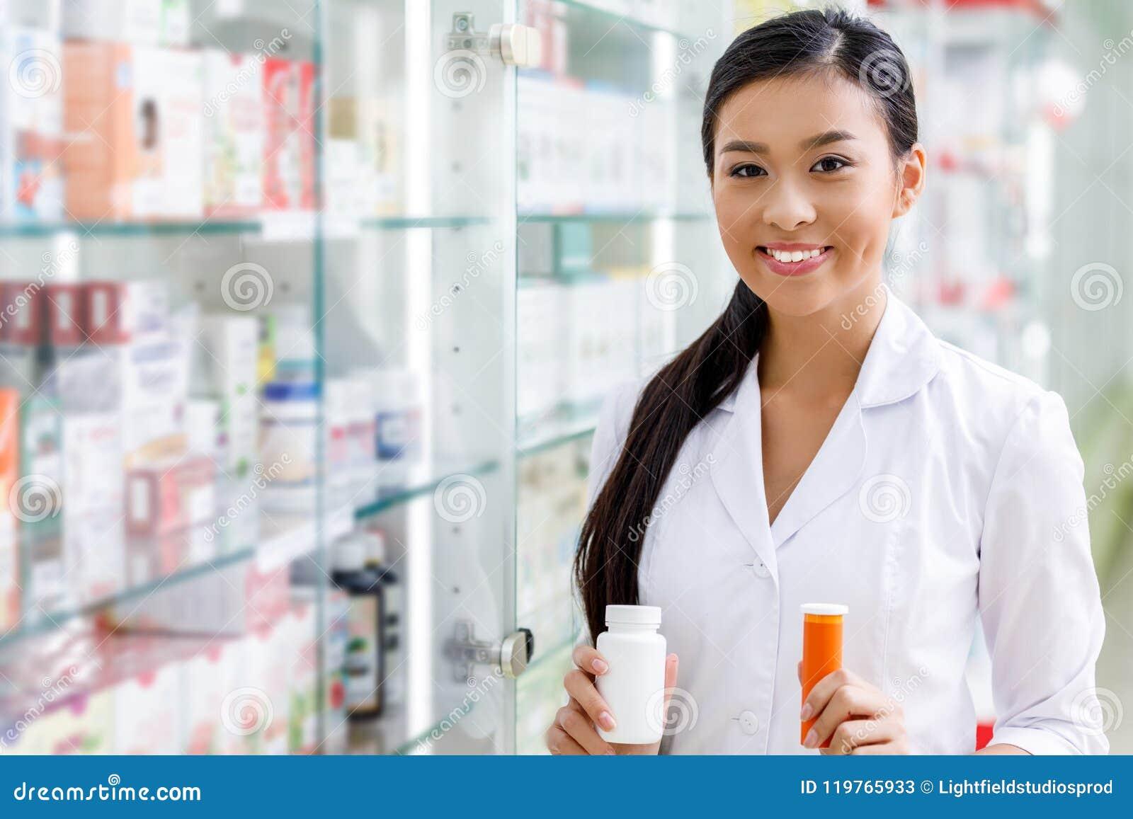 Farmacêutico novo que guarda recipientes com medicamentação e que sorri na câmera