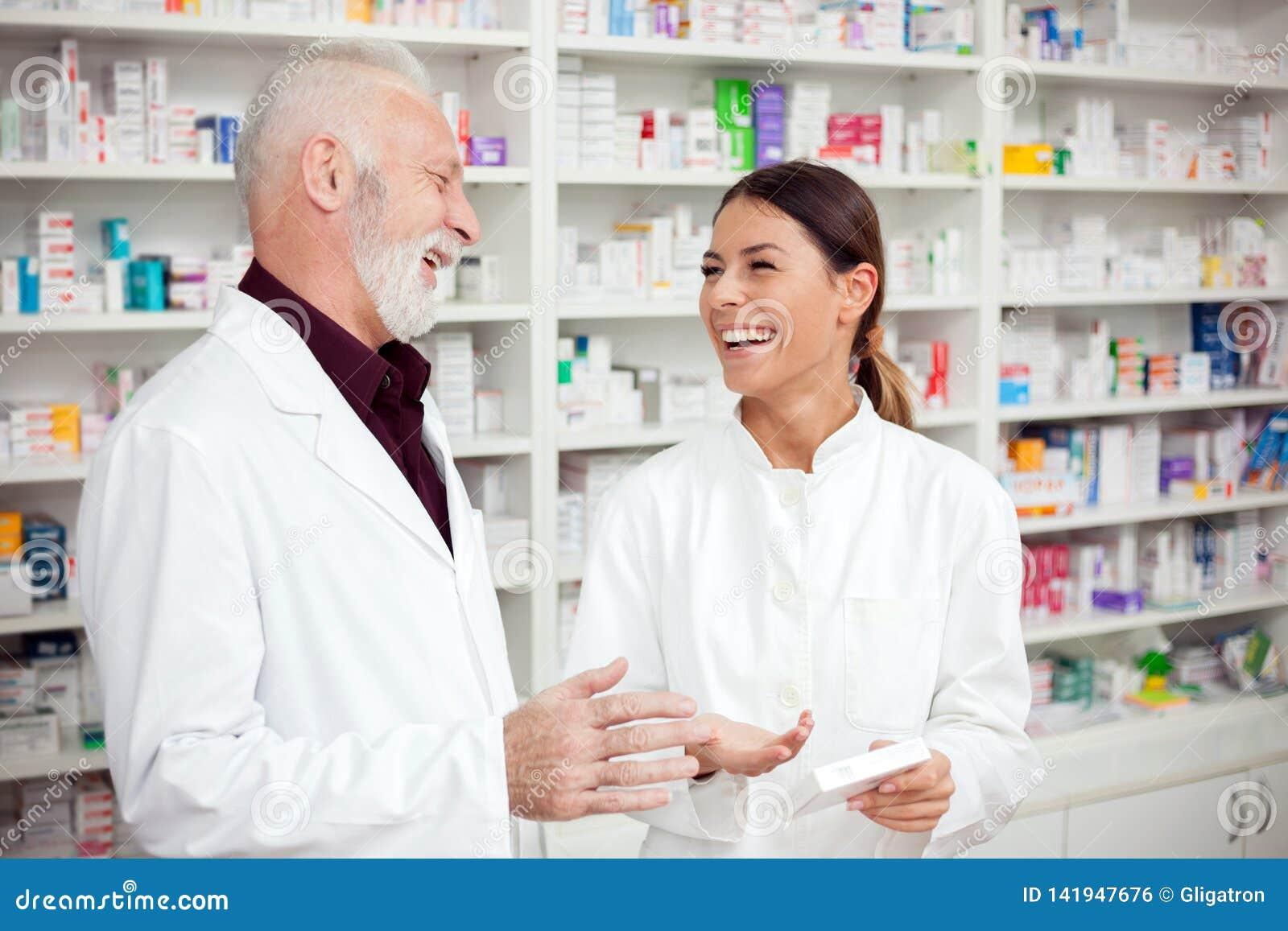 Farmacêuticos masculinos fêmeas e superiores novos felizes que estão na frente das prateleiras com medicamentações e fala