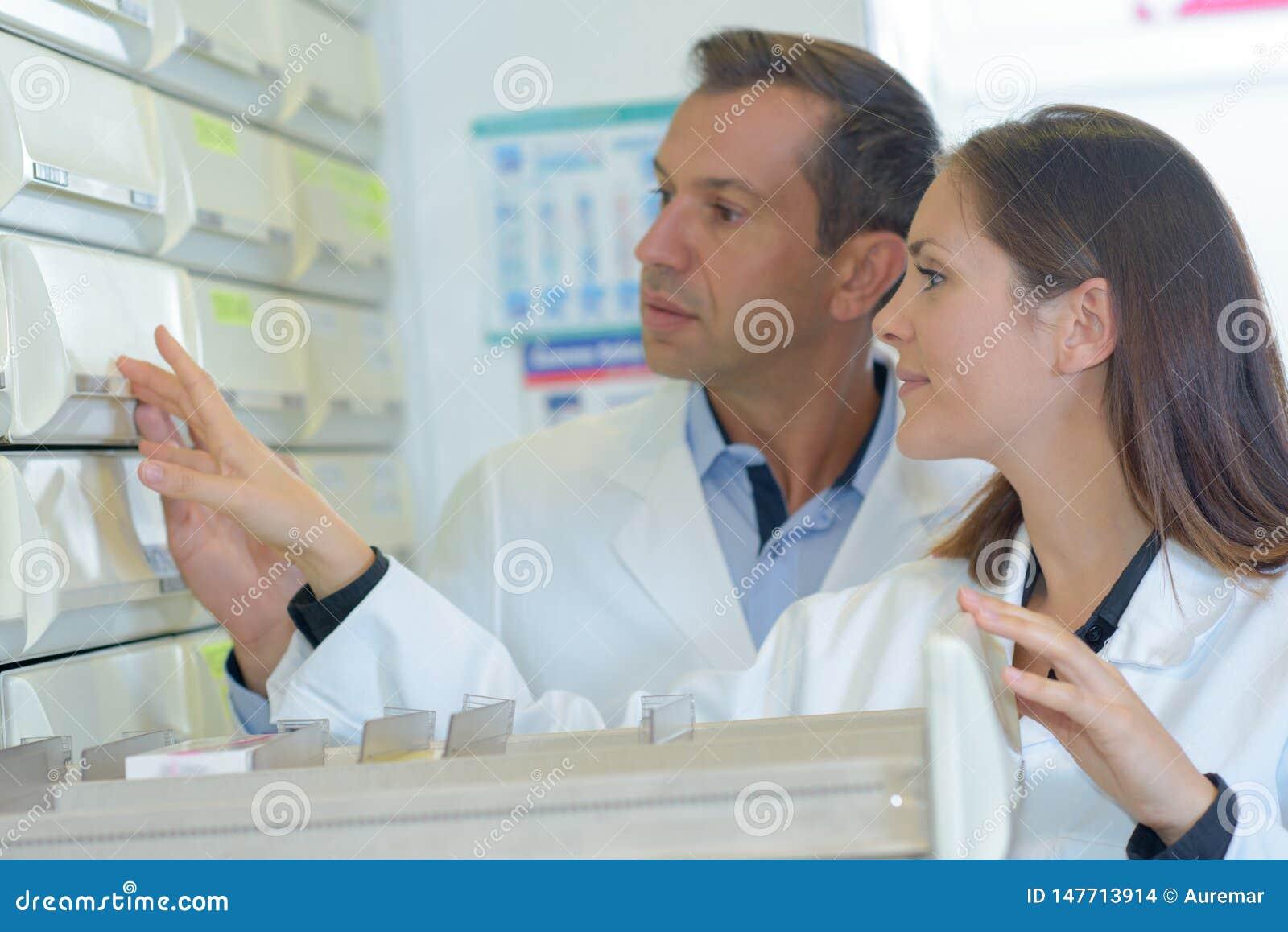 Farmacêuticos que olham a medicamentação na gaveta