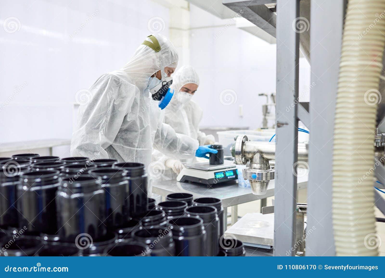 Farmaceutische Installatiearbeiders die Schaal gebruiken