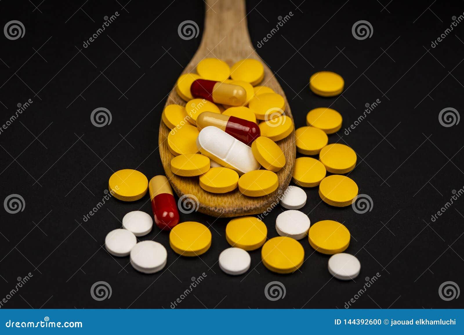 Farmaceutiska medicinpiller, på träskeden på svart bakgrund