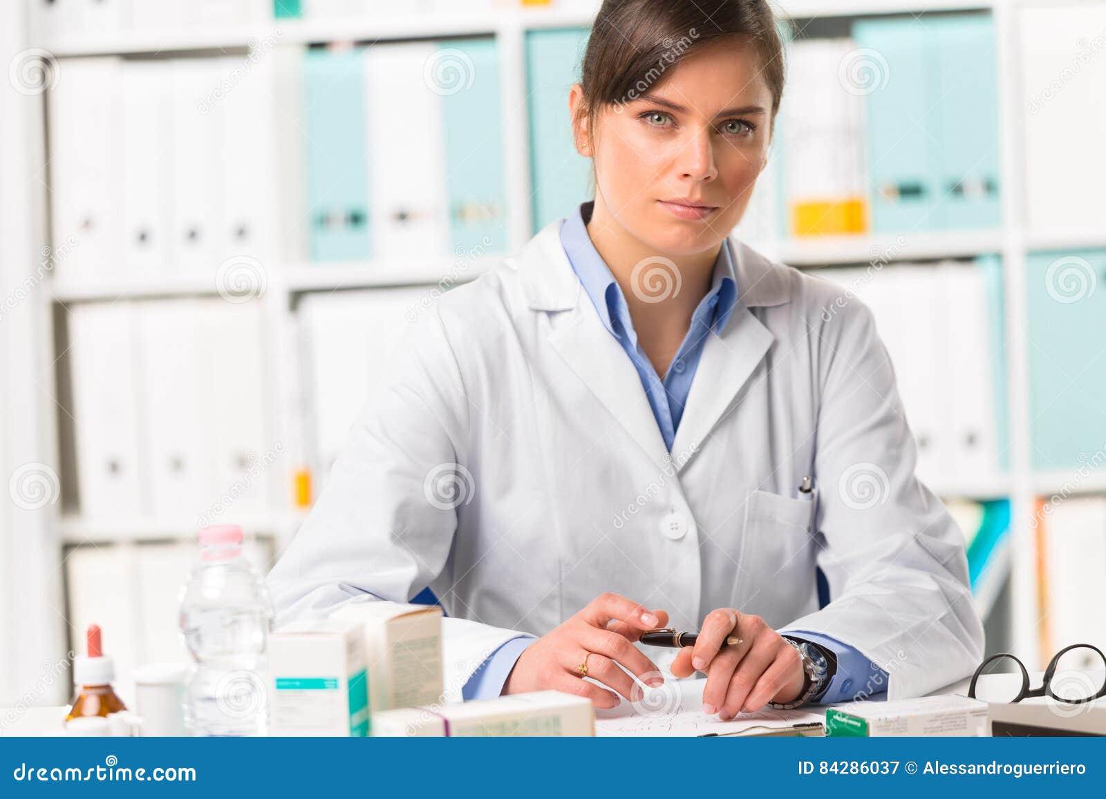 Farmacista femminile seduto alle note di scrittura dello scrittorio